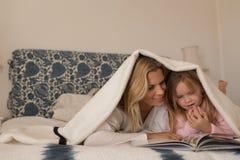 Matka z jej córki czytelniczym storybook pod koc w sypialni zdjęcia stock
