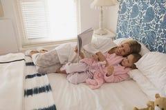 Matka z jej córki czytelniczym storybook w sypialni fotografia royalty free
