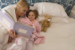 Matka z jej córki czytelniczym storybook w sypialni zdjęcie stock