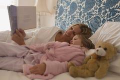 Matka z jej córki czytelniczym storybook w sypialni zdjęcia stock