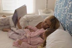 Matka z jej córki czytelniczym storybook w sypialni zdjęcie royalty free