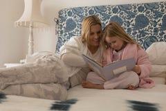 Matka z jej córki czytelniczym storybook w sypialni obrazy stock