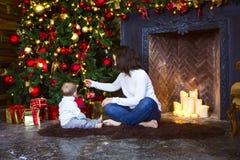 Matka z jej chłopiec jest usytuowanym blisko choinki Zdjęcie Royalty Free