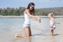 Matka z jej dzieckiem ma zabawę na plaży Zdjęcia Stock