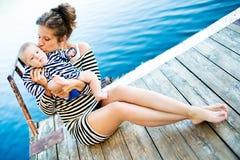 Matka z jej dzieckiem zabawę blisko jeziora Obraz Royalty Free