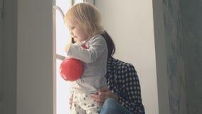 Matka z jej małą dziewczynki pozycją blisko przyglądającego outside i okno zbiory wideo