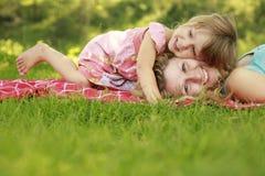 Matka z jej małym córki kłamstwem na trawie Obrazy Stock