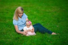 Matka z jej małym dzieckiem siedzi na zielonej trawie Obrazy Royalty Free