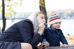 Matka z małymi syna dmuchania bąblami Fotografia Stock