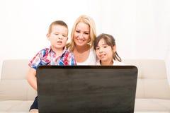 Matka z ona dzieciaki używa laptop obraz royalty free