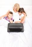 Matka z ona dzieciaki używa laptop w łóżku zdjęcie royalty free