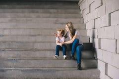 Matka z syna obsiadaniem na schodki obraz stock