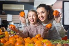 Matki i blondynki córki kupienia mandarynki w sklepie Fotografia Royalty Free