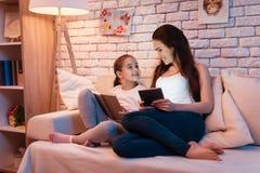 Matki i córki czytelnicza książka i bawić się na pastylce na laptopie przy nocą w domu Obrazy Royalty Free