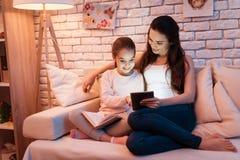 Matki i córki czytelnicza książka i bawić się na pastylce na laptopie przy nocą w domu Obraz Royalty Free