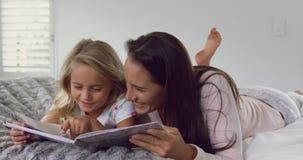 Matki i córki czytelnicza opowieść rezerwuje na łóżku w sypialni przy wygodnym domem 4k zdjęcie wideo