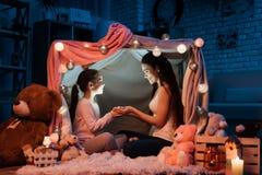 Matki i córki mienia latarka ich ręki w poduszka domu póżno w domu przy nocą Obrazy Royalty Free