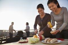 Matki i córki narządzania hot dog dla grilla, ojca i syna narządzania kiełbas na grillu, Zdjęcie Royalty Free