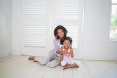 Matki i córki obsiadanie na podłogowym pokazuje nowego domu kluczu Obrazy Stock