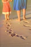 Matki i córki odprowadzenie na plażowym opuszcza odcisku stopy w piasku Zdjęcie Royalty Free