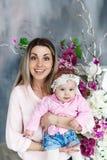 Matki i córki uścisk Piękna kobieta z dzieciak dziewczyną Pracowniany portret z kwiatami Kobieta model Obrazy Stock