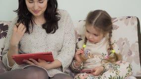 Matki i córki uses gadżety siedzi przy kanapą w domu zbiory