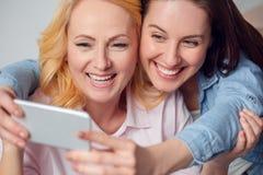 Matki i córki weekend siedzi wpólnie w domu brać selfie obrazków śmiać się Obraz Stock