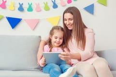 Matki i córki wpólnie w domu weekend siedzi trzymający cyfrowe pastylki dopatrywania kreskówki Obraz Royalty Free