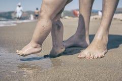 Matki i dziecka cieki chodzi na piasku wyrzucać na brzeg Obrazy Royalty Free