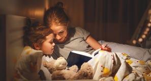Matki i dziecka czytelnicza książka w łóżku przed iść spać Zdjęcie Royalty Free