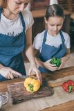 Matki i dziewczyny przecinania pieprze na kuchni obrazy royalty free