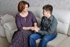 Matki i syna chwyta spojrzenie przy each inny i ręki Zdjęcie Stock