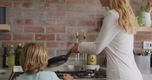 Matki i syna narządzania jedzenie w kuchni przy wygodnym domem 4k zbiory