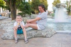 Matki i syna obsiadanie na skale Obrazy Royalty Free