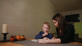 Matki i syna obsiadanie w kuchni jego uczenie i zbiory wideo