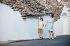 Matki i syna odprowadzenie zwęża się ulicy ot typowego włoskiego miasteczko Zdjęcia Stock
