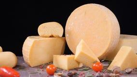 Matkonstbegrepp Ostvänner Variation av ost som förläggas på träbräde med svart bakgrund rosmarin hälls från stock video