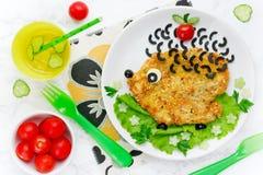 Matkonstidén för ungar äter lunch - den fega schnitzeln med grönsaker arkivfoton