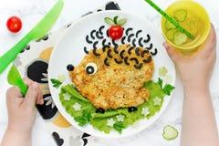 Matkonstidén för ungar äter lunch - schnitzeln med formade grönsaker arkivbild
