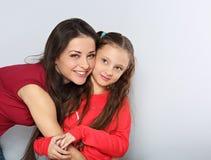 Matkuje dziewczyny przytulenie z szczęśliwymi emocjonalnymi twarzami na błękitnym tle z pustą kopii przestrzenią i żartuje zdjęcie stock