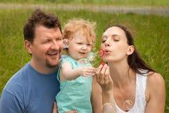 Matkuje i ojcuje i córki dmuchanie gulgocze outdoors w summe Fotografia Stock