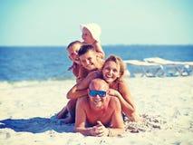 Matkuje i ojcuje z trzy dziećmi na plaży Fotografia Royalty Free