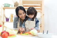 Matkuje tnących warzywa i żartuje dziewczyny kucharstwo i Obrazy Stock
