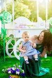 Matkuje z młodą córką na jej podołku siedzi na trawie w jardzie przeciw tłu cukierku bar Zdjęcia Royalty Free