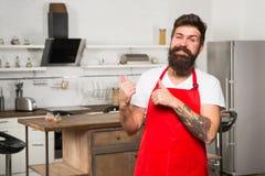 Matlagning är mitt liv Skäggig man i rött förkläde Restaurang- eller kafékock Hipster i kök mogen manlig Skäggig mankock arkivfoton