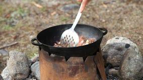 Matlagning av kött i kittel utomhus arkivfilmer
