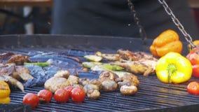 Matlagning av korvar och grönsaker på gallret lager videofilmer