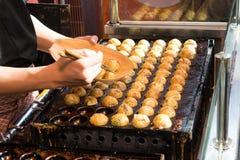 Matlagning av Takoyaki en av den populäraste maten i Osaka arkivbild
