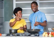 Matlagning för afrikansk amerikanförälskelsepar på kök royaltyfri fotografi