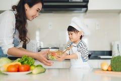 Matlagning för barnportionmoder i modernt kök Arkivbilder